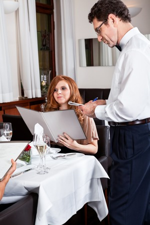 man and woman for dinner in restaurant waiter serving mineral water  photo