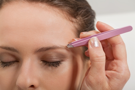 plucking: young beautiful woman eyebrow plucking tweezers eyes hair  closeup portrait