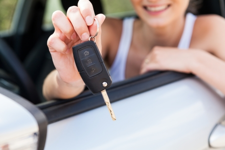 key handover: young smiling woman sitting in car taking key handover rent  purchase