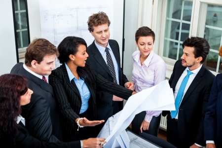 business people discussing architecture plan sketch in office photo