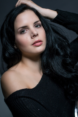 tantalising: Dark moody portrait of a sultry beautiful woman with long black hair wearing a stylish off the shoulder top , head and shoulders against a grey studio background