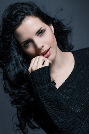 sultry: Dark moody portrait of a sultry beautiful woman with long black hair wearing a stylish off the shoulder top , head and shoulders against a grey studio background