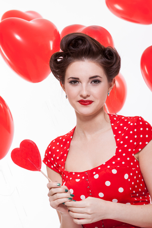 french roll: Beautiful retro woman with a French roll hairstyle celebrating Valentines Day dressed in a red polka dot dress and holding a red heart while looking at the camera with a gentle smile