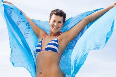 Carefree beautiful young woman in a bikini running and leaping on a beach with a pretty turquoise blue scarf floating out in the air behind her as she celebrates her freedom during the summer vacation