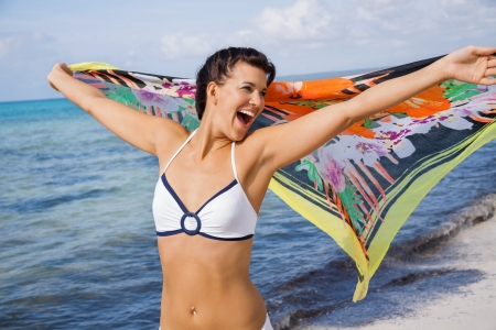 exuberant: Laughing vivacious woman in a bikini at the seaside holding a colourful patterned scarf in her outstretched hands to flutter in the breeze against an ocean backdrop