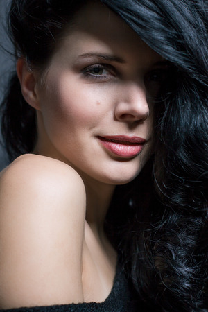 Dark moody portrait of a sultry beautiful woman with long black hair wearing a stylish off the shoulder top , head and shoulders against a grey studio background