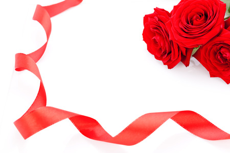 courting: Bouquet of beautiful fresh red roses with a coiled ribbon border isolated on white with plenty of copyspace for your loving anniversary or Valentines message