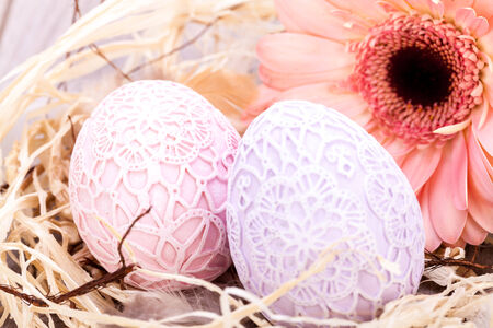 easter egg hunt: Beautiful pastel coloured Easter eggs in handcrafted intricate crocheted covers with a fresh pink Gerbera daisy in a clean straw nest for a traditional symbolic Easter celebration