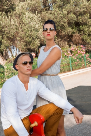 unemotional: Elegant trendy young couple in fashionable modern clothes and accessories posing outdoors in the summer sunshine in a garden or park