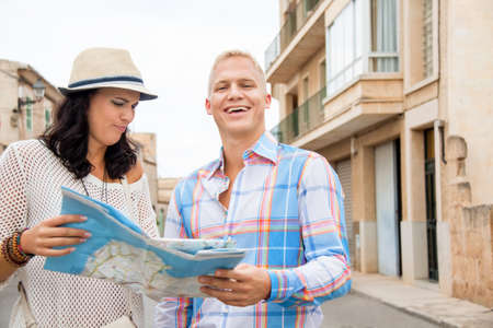 Trendy attractive young couple of tourists consulting a map as they search for their destination while out sightseeing on their summer vacation photo