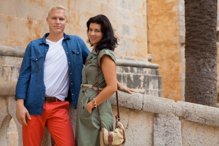unemotional: Young attractive couple in summer fashion standing together on the shallow stone steps of a bridge looking back at the camera with serious expressions, candid natural shot