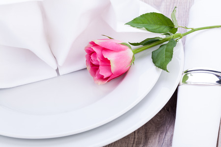 Romantic formal elegant table setting with a single pink rose and decorative ribbon for a sweetheart on Valentines Day