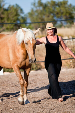 young woman training horse outside in summer choreography  Фото со стока