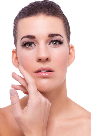 Beautiful naked woman with her hair tied back and a serene expression in a thoughtful pose with her hand to her chin, close up head and shoulders portrait on white Stock Photo