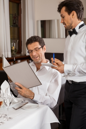 Waiter serving a young couple seated at a table holding menus in a restaurant waiting as they make their choice and place their order 写真素材