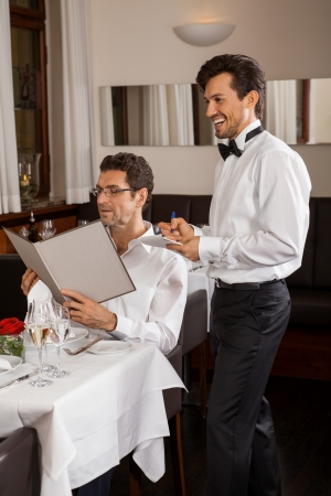 Waiter serving a young couple seated at a table holding menus in a restaurant waiting as they make their choice and place their order photo