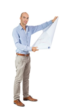 Architect or structural engineer standing reading an unrolled blueprint of the design which he is holding open in his hands, side view isolated on white photo