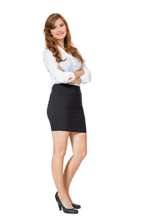 Attractive self-assured trendy young businesswoman wearing high heels and a black miniskirt standing with folded arms smiling at the camera, side view isolated on white photo