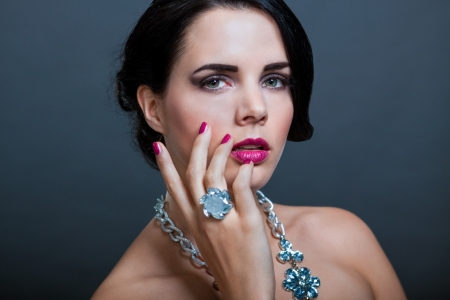 Beautiful sophisticated dark haired woman wearing elegant showy gemstone jewellery posing with bare shoulders and her hand raised gracefully to her downcast eyes with a serene expression photo