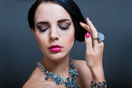 downcast: Beautiful sophisticated dark haired woman wearing elegant showy gemstone jewellery posing with bare shoulders and her hand raised gracefully to her downcast eyes with a serene expression