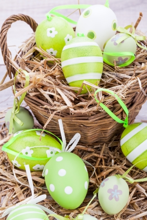 frailty: Collection of four hand decorated colourful green Easter eggs with different patterns displayed in straw, close up view