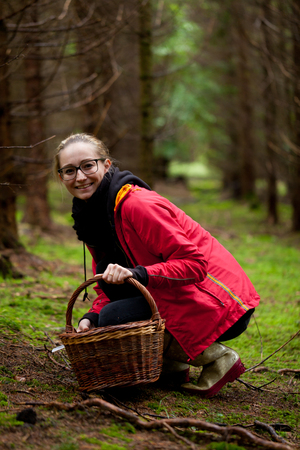 young woman collecting mushrooms in forest autumn nature photo