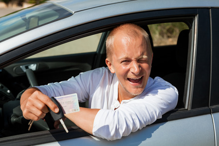 Portrait of an excited Caucasian male driver holding the keys of his new modern car and his driving license photo