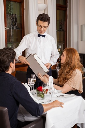 Kellner serviert ein junges Paar sitzt an einem Tisch hält Menüs in einem Restaurant warten, wie sie ihre Wahl und legen Sie die Reihenfolge