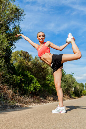 young attractive athletic woman stretching fitness summer photo