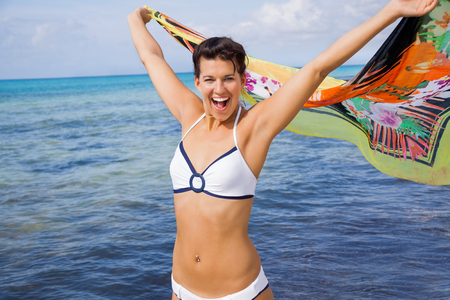 flutter: Laughing vivacious woman in a bikini at the seaside holding a colourful patterned scarf in her outstretched hands to flutter in the breeze against an ocean backdrop