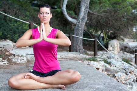 Attractive young woman with a serene expression sitting barefoot meditating in the lotus position outdoors in a park photo