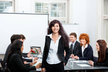professional successful smiling business woman in office with team in background photo