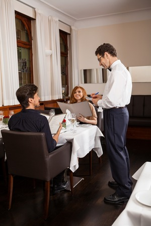Waiter serving a young couple seated at a table holding menus in a restaurant waiting as they make their choice and place their order Фото со стока