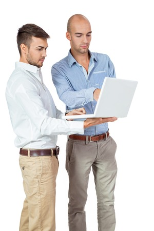 computer support: Two businessmen consulting a landheld laptop computer as they hold a discussion about the information on the screen, isolated on white