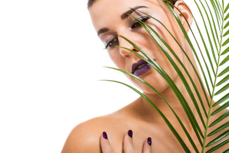 Portrait of a sensual beautiful naked woman holding a fresh palm frond with her hand with manicured purple nails resting gracefully on her shoulder as she looks down with a serious serene expression photo