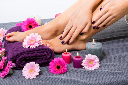 Overhead view of the bare feet of a woman with beautiful manicured red nails resting on a purple towel surrounded by fresh colourful pink gerbera daisies in a spa or beauty salon Stock Photo
