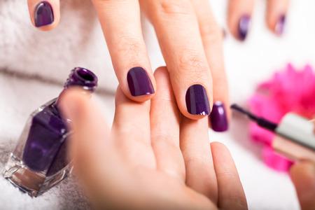 어플리케이터 풍부한 보라색 손톱 광택을 적용하는 미용사의 근접 촬영 볼 수있는 뷰티 살롱에서 네일 매니큐어를 가진 여자