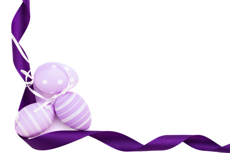 Easter background with three traditional eggs, painted in pastels, with stripes and dots, decorated with a mauve ribbon, on white photo