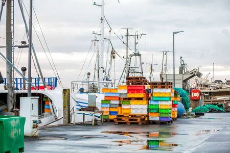 superstructure: Fishing boat in harbour docked at the quay with just its superstructure and radar navigation equipment visible with brightly coloured trays for the catch stacked on the dock