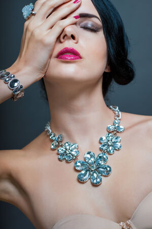 Beautiful sophisticated dark haired woman wearing elegant showy gemstone jewellery posing with bare shoulders and her hand raised gracefully to her downcast eyes with a serene expression