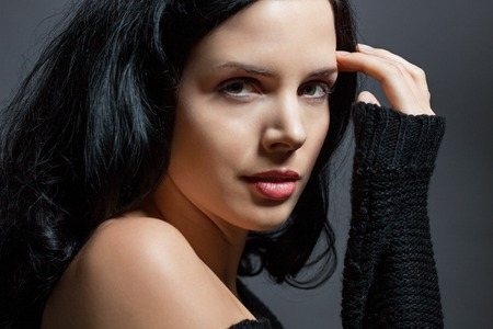 inscrutable: Dark moody portrait of a sultry beautiful woman with long black hair wearing a stylish off the shoulder top , head and shoulders against a grey studio background