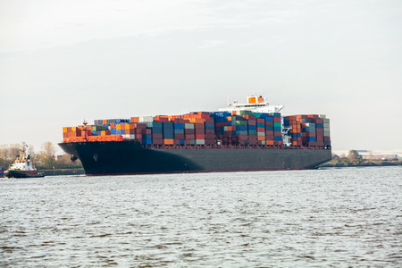 removals: Fully laden container ship in port with its decks stacked with metal containers full of freight and cargo for international destinations
