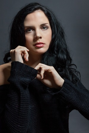 Dark moody portrait of a sultry beautiful woman with long black hair wearing a stylish off the shoulder top , head and shoulders against a grey studio background photo
