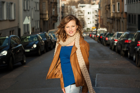 Beautiful trendy young woman with a lovely smile in a long flowing scarf standing in a shaft of sunlight in an urban street with parked cars and townhouses photo