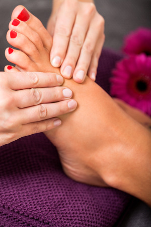 cleanse: Woman having a pedicure treatment at a spa or beauty salon with the pedicurist massaging the soles of her feet with a pumice stone to cleanse dead skin and stimulate the tissue