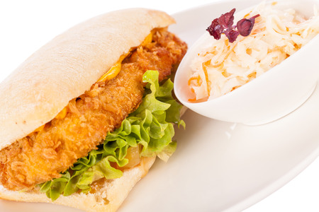 Closeup of a tasty burger with a golden crispy crumbed chicken breast topped with melted cheese and fresh curly lettuce on a white crusty roll photo