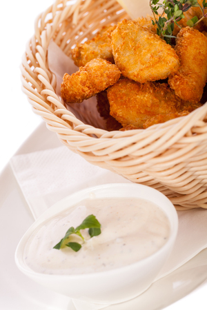 nuggets de pollo: Crispy fried empanadas nuggets de pollo en una canasta de mimbre servida como un dedo o un aperitivo con un dip cremoso en un bol junto con Foto de archivo