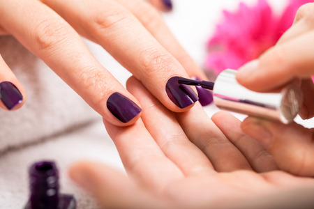 nail polish bottle: Woman having a nail manicure in a beauty salon with a closeup view of a beautician applying rich purple nail varnish with an applicator
