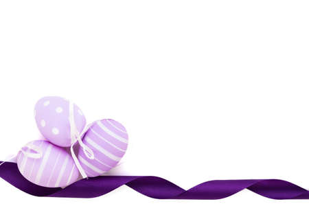 Easter background with three traditional eggs, painted in pastels, with stripes and dots, decorated with a mauve ribbon, on white Stock Photo