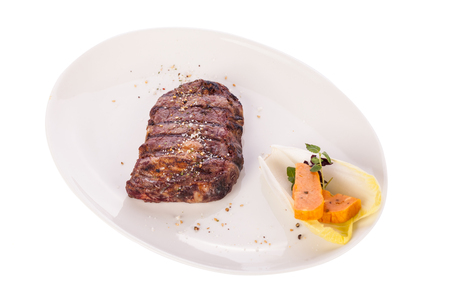 seasoned: Delicious trimmed lean portion of thick grilled beef steak with seasoning served on a white plate, close up with shallow dof